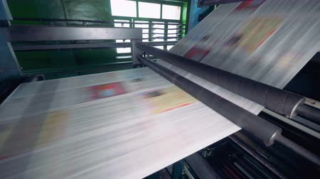 nakladatelství : Printing equipment moves paper sheets on a line at a factory. 4K.