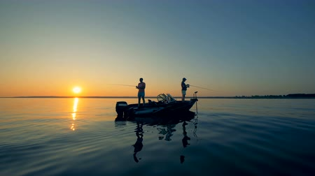 outdoor hobby : Sunrise waterscape of several men fishing