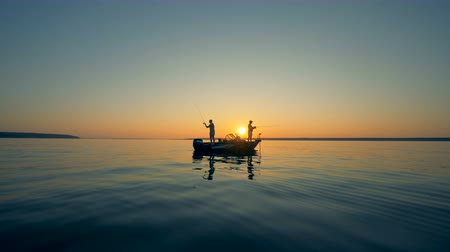 fishing pole : Male silhouettes while fishing from a motorboat during sunrise