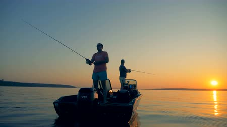 fishing pole : Men are catching fish from an autoboat in the open water