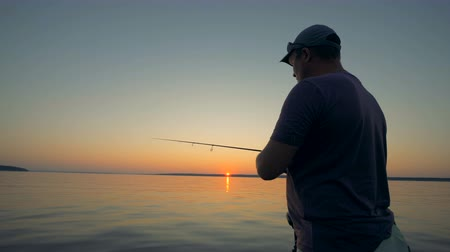 yakalandı : Adult male fisherman in the process of angling during sunrise Stok Video