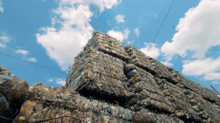 preslenmiş : Recycling materials at a dump, bottom view. Big stacks of plastic bottles lay at a junkyard.