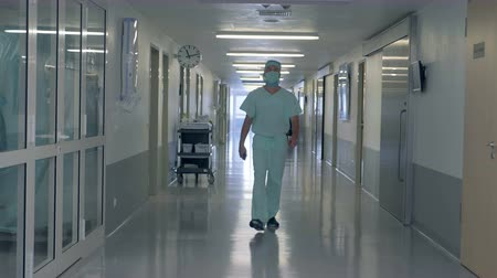 intensive care unit : Adult male doctor is passing by the hospital hall Stock Footage