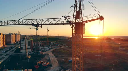 realty : Construction site on a sunset background. Tower crane at a construction site. Stock Footage