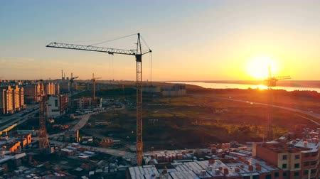 külvárosok : A construction site on the outskirts. Construction crane at sunset background. Stock mozgókép
