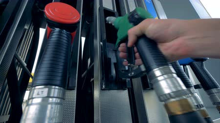 benzine : Close up of human hand putting out a green fuel nozzle. Gasoline fuel, gas station concept.
