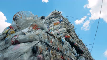 premente : Recycling plant with lots of garbage. Plastic wraps and bottles pressed in stacks for recycling.