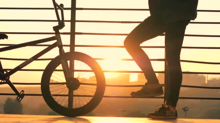 handrails : Man stands with a bike on a sunset background, close up.