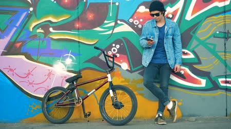 grafiti : Rider stands with a phone in hands. Young stylish Caucasian male teenager.