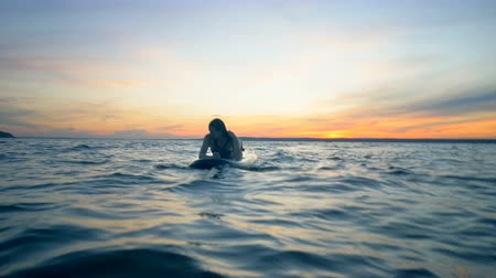 sup : Freedom concept. Young Attractive Woman is lying on a paddleboard in the open water during sunset