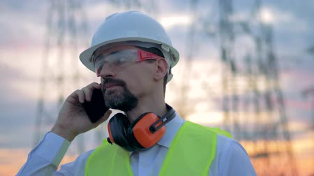 glass master : A male electrician talks on a mobile phone near power lines. Stock Footage