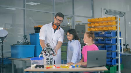 старшей школе : Male research associate is showing two kids how a robot works