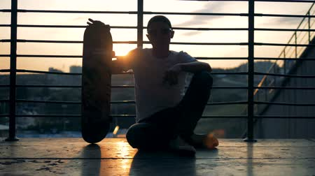 construir : A skateboarder sits on a sunset background, close up. Stock Footage
