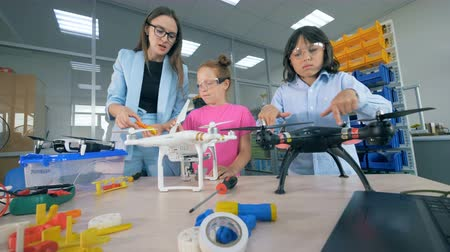 constructing : Blades of quadcopters are getting rotated by kids and a lab specialist