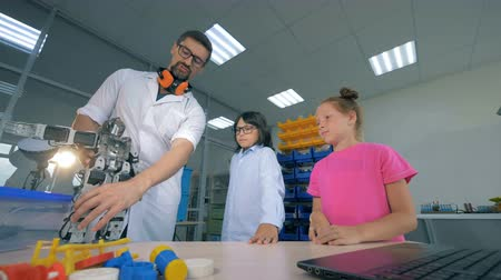 проведение : Demonstration process of a toy robot to the children carried out by a male professional