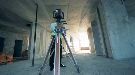 geodesy : Architect with tablet uses a walkie talkie, standing in the unfinished building.