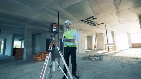 realty : Builder uses special equipment at a construction site, close up. Stock Footage