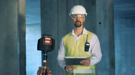 geodesy : Builder, engineer types on a tablet working on a construction site.