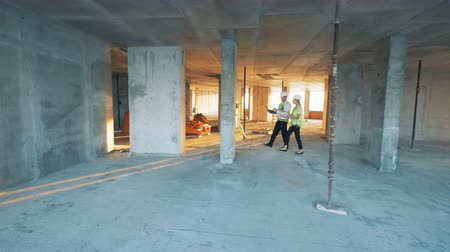 geodesy : Engineers walk through a building on a construction site.