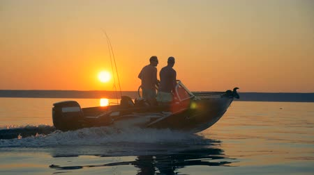halászok : Two fishermen are moving across sunrise waterscape on a speedboat