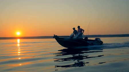 ужение : Sunrise scenery with two anglers driving a motorboat. Friendship, best friends concept.