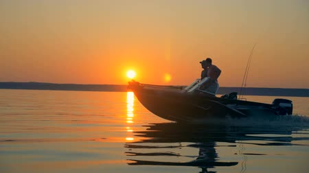 equipped : Two fishermen are driving a speedboat in the sunrise landscape. Friendship, best friends concept.