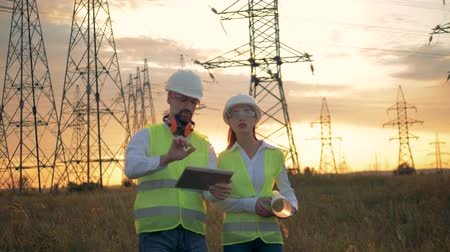 job transfer : Professional engineers walking through a field near electrical line.