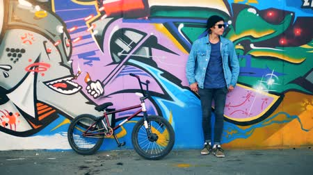 urbanística : Male teenager is standing against the graffiti wall with a bicycle