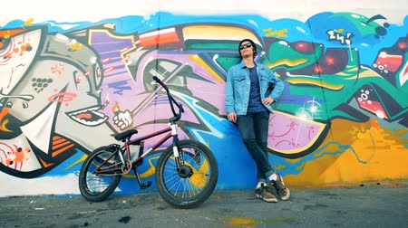 urbanística : Male cyclist is leaning on a graffiti wall with his bike being near it Vídeos