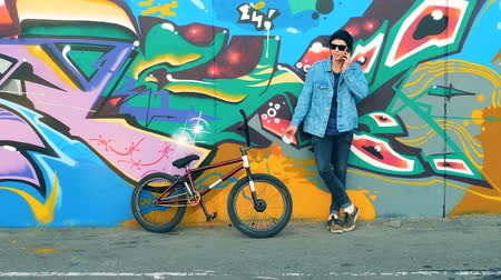 urbanística : Graffiti wall and a young cyclist standing against it and talking on the phone Vídeos