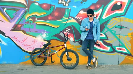 urbanística : Young man with a cell phone is standing near a street wall and his BMX Vídeos