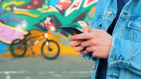 urbanística : Close up of male hands with a smartphone with a bike and a graffiti in the background