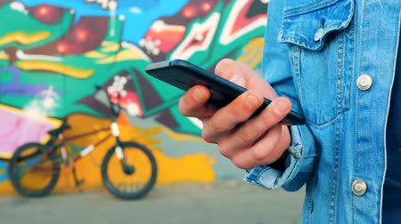 urbanística : Cell phone in a hand of a man standing close to a graffiti wall and a bicycle