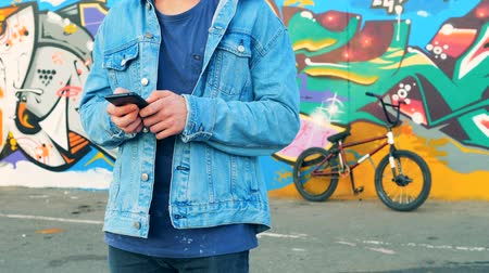 urbanística : Male teenager is standing near his BMX and a street wall with a smartphone in his hands
