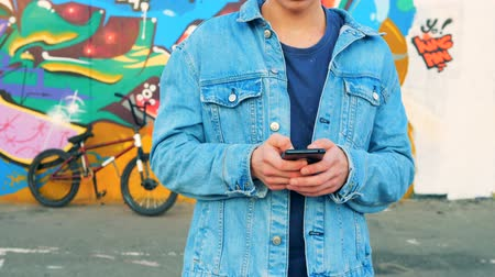urbanística : Teenager in a jeans jacket is standing with his mobile phone near a graffiti wall