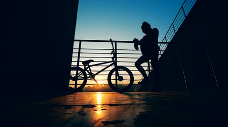 urbanística : Silhouettes of a young man and his bicycle in the setting sun