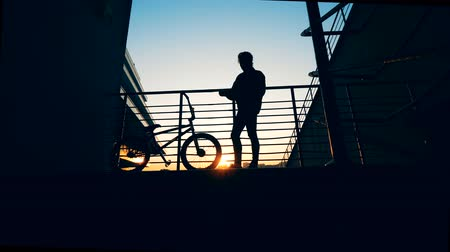 urbanística : Platform in sunset with a young man doing his hair and a bicycle standing beside him