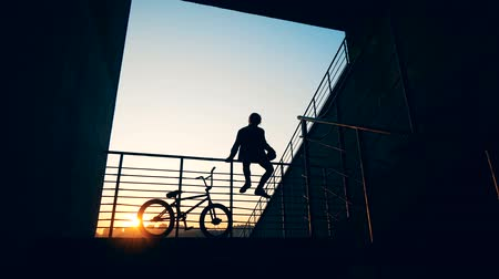 urbanística : Silhouette of a young man sitting on railings with a bike near him in the setting sun Vídeos