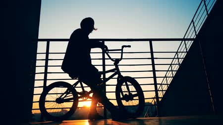 urbanística : Male teenager is sitting on his bicycle in the rays of the setting sun and taking off his hat Vídeos
