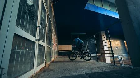urbanística : Male teenager is doing a stunt on his bicycle in an empty building
