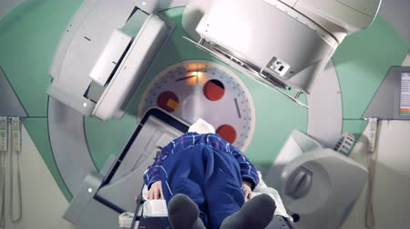 oncologia : A man is getting radiated by a linear accelerator. Medical technology concept. Filmati Stock