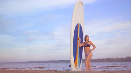 sörf : Gorgeous lady is standing with a board at the seashore
