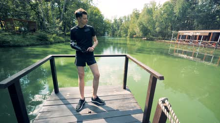 робот : Young man in sportswear with a robotic bionic arm and a cellphone is standing on a river bridge