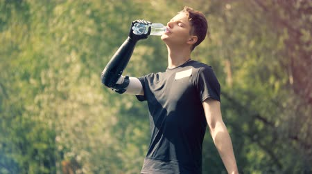 challenged : Teenager is holding a bottle with his prosthetic hand and drinking from it outdoors