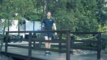 sintético : Male teenager with a prosthetic arm is walking along the bridge Stock Footage