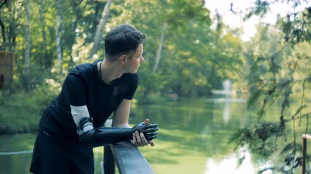 power equipment : Young man with a bionic arm is standing near river bridge Stock Footage