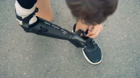 challenged : Sneakers shoelaces are getting tied by a man with a prosthetic hand Stock Footage