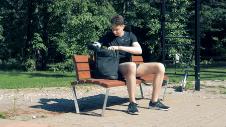 challenged : Teenager is taking a laptop out of the bag with his prosthetic hand while sitting on a bench Stock Footage