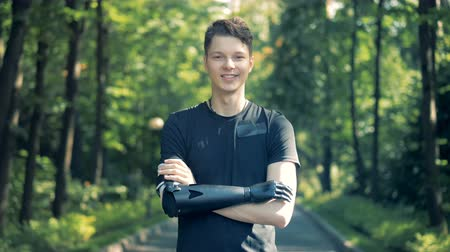 challenged : Teenage boy with a futuristic bionic prosthetic arm is standing in a park and smiling at the camera.