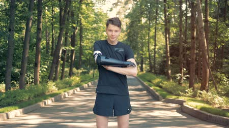 physically : A young man with bionic arm in park. Futuristic human cyborg concept. Stock Footage